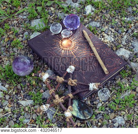Magic Book Of Spells Or Fairy Tales With Crystals And Pentagram On The Grass In The Garden. Esoteric