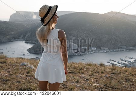 Happy Woman Travels In A White Dress In The Highlands And Enjoys A Beautiful View Of A Quiet Bay Dur