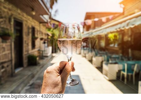 Glass Of Wine In Hand. A Glass Of Young Fresh Rose Wine Against The Backdrop Of A Summer Cafe In A M