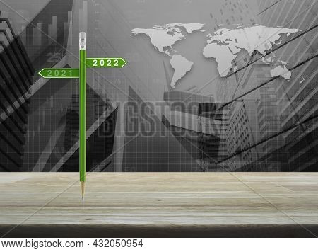 2022 And 2021 Direction Sign Plate With Green Pencil On Wooden Table Over World Map With Financial G