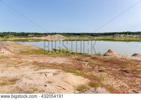Shallow Lake On The Site Of The Abandoned Quarry Of Ilmenite Ore Against The Forest And Clear Sky In