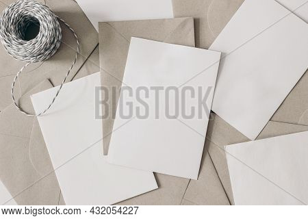 Pile Of Blank Letters With Craft Envelopes And Decorative Rope On Table. Closeup Of Empty Greeting C