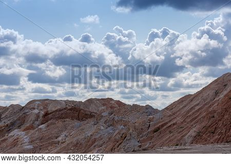 Old Colored Rock Dumps In Quarry For The Extraction Of Ilmenite Ore Against The Sky With Clouds In B