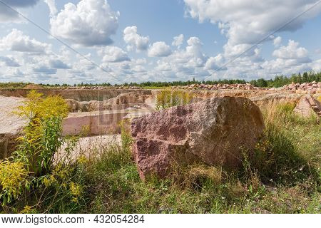 Piles Of Stones Lie Around Of Granite Quarry With Blocks Of Red Granite On A Foreground  In Summer