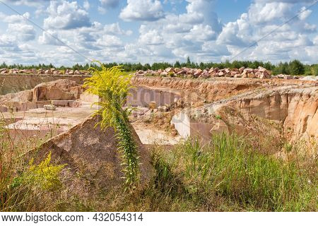 Block Of Red Granite Lie Among The Different Flowering Grass On A Blurred Background Of Granite Quar