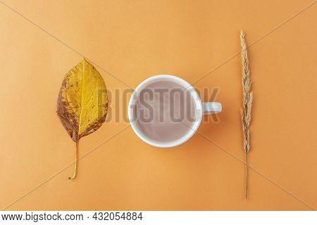 Autumn Still Life With Cup Of Coffee And Yellow Fall Dry Leaves On Orange Background. Minimal, Styli