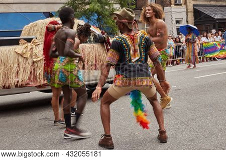 June 24, 2018 Gay Parade, New york. The company of afroamerican dancing authentic dance at the pride parade  on the street.  Focus on back of afro man