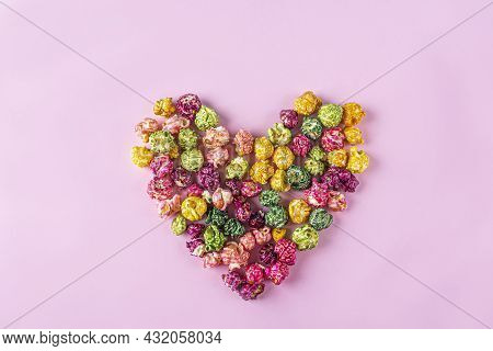 Love Movies Concept. Colorful Rainbow Caramel Candy Popcorn Scattered On Pink Background, Heart Shap
