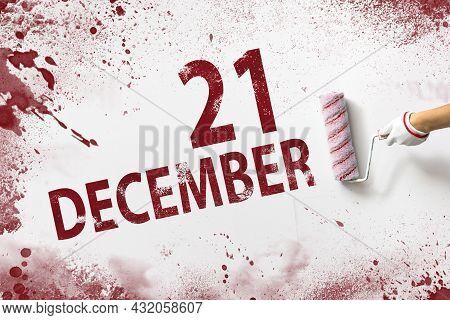 December 21st . Day 21 Of Month, Calendar Date. The Hand Holds A Roller With Red Paint And Writes A