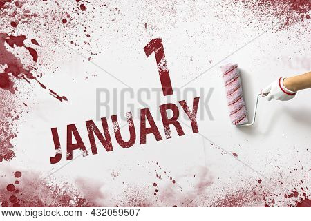 January 1st . Day 1 Of Month, Calendar Date. The Hand Holds A Roller With Red Paint And Writes A Cal