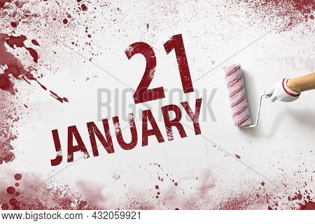 January 21st . Day 21 Of Month, Calendar Date. The Hand Holds A Roller With Red Paint And Writes A C