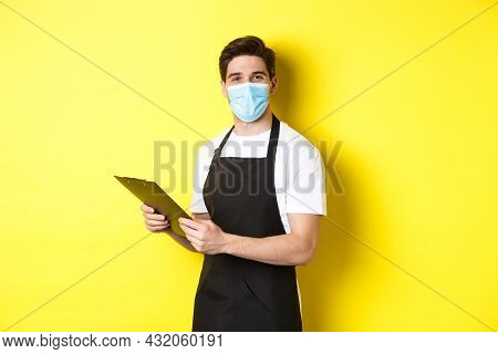 Concept Of Covid-19, Small Business And Quarantine. Young Male Seller In Medical Mask And Black Apro