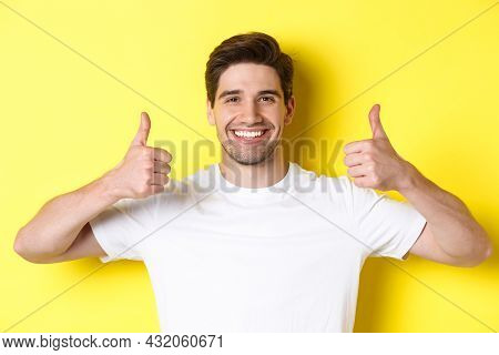Close-up Of Handsome Young Man Showing Thumbs Up, Approve And Agree, Smiling Satisfied, Standing Ove