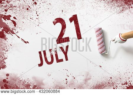 July 21st . Day 21 Of Month, Calendar Date. The Hand Holds A Roller With Red Paint And Writes A Cale