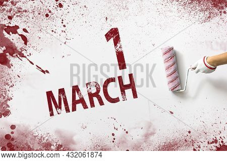 March 1st . Day 1 Of Month, Calendar Date. The Hand Holds A Roller With Red Paint And Writes A Calen