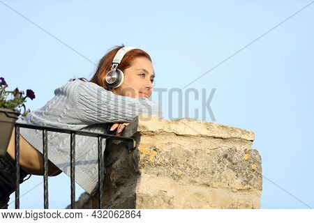 Happy Woman Contemplating From Balcony Listening To Music With Headphones
