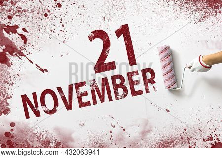 November 21st . Day 21 Of Month, Calendar Date. The Hand Holds A Roller With Red Paint And Writes A