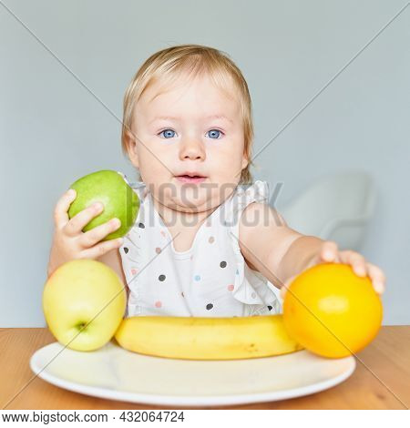 Funny Blond Blue-eyed Child Holding Green Aple And Reaching For Orange. Healthy Food. Plate With Fru