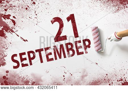 September 21st . Day 21 Of Month, Calendar Date. The Hand Holds A Roller With Red Paint And Writes A