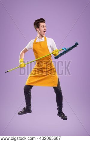 Full Body Of Comic Energetic Young Man In Yellow Apron And Rubber Gloves Holding Mop Ready To Clean