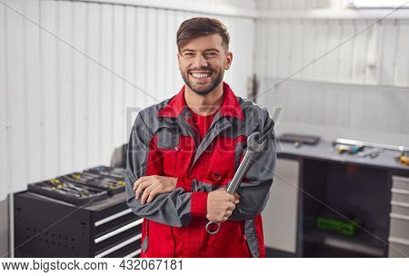 Happy Young Bearded Male Master In Workwear With Spanner Wrench Looking At Camera While Standing In