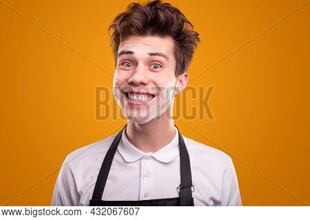 Funny Young Guy In Black Apron And White Shirt Smiling Frantically And Looking At Camera After Washi