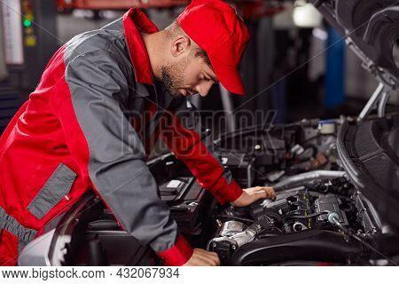 Side View Of Professional Repairman In Workwear Standing Near Open Hood Of Modern Automobile And Exa