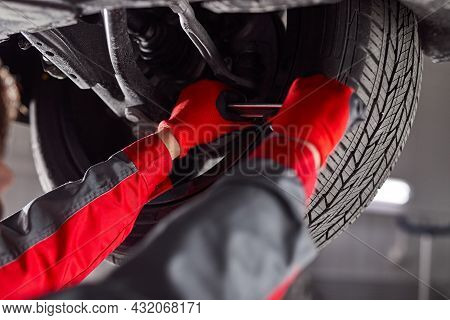 Soft Focus Of Crop Male Technician Using Tool To Detach Wheel While Repairing Vehicle In Professiona