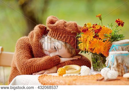 Adorable Little Girl On Picnic In Autumn Park. Smiling Little Girl  Having Tea Party Outside In The