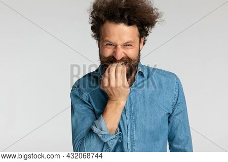 funny casual model in denim shirt with long beard and curly hair holding fingers to mouth, biting and making silly faces on grey background in studio