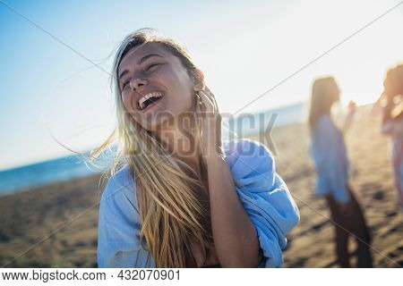 Happy Young Woman On The Beach With Her Friends In Background. Group Of Friends Having Fun On Beach