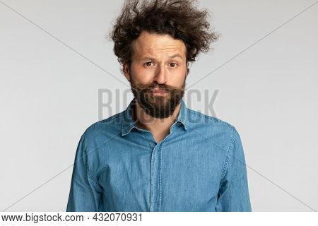 portrait of casual relaxed young man with curly hair and beard making funny faces and posing on grey background in studio