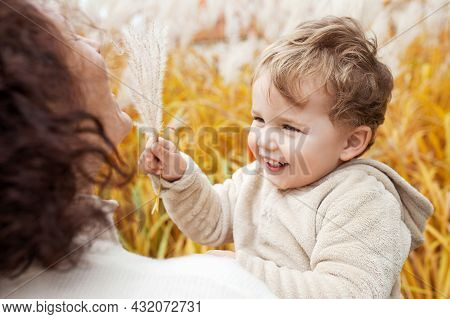 Happy Mother And Her Little Child In The Park. Child Playing With Mother's Hair. Mother And Son Embr