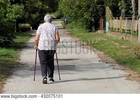 Old Woman Walking With A Cane On A Street. Limping Person, Diseases Of The Spine, Life Of Elderly Pe