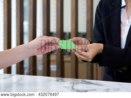 The Hotel Manager In The Suit Handed A Room Card To The Guest. Close Up