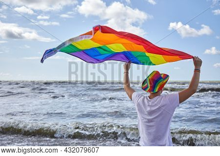 Man Standing By The Sea And Holding The Lgbtq Pride Flag. Lgbtq Concept