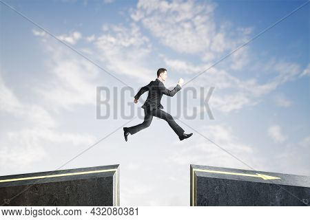 Side View Of Businessman Jumping Over Gap On Sky Background With Mock Up Lace. Challenge And Success