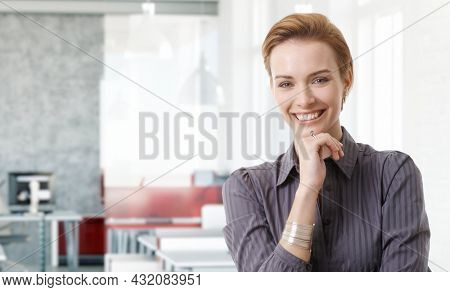 Confident young white businesswoman smiling in modern business office. Portrait of adult woman in 20s, happy confident smile. Copy space.