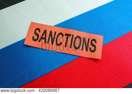 Russian Flag And Word Sanctions As Symbol Of Economical Restrictions.