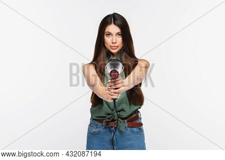 Young Woman With Shiny Hair Holding Hair Dryer While Aiming Isolated On Grey