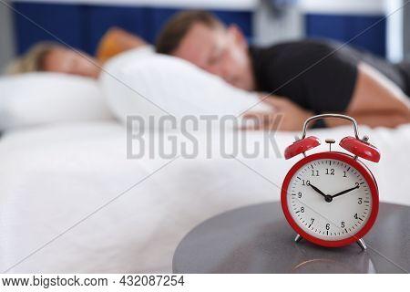 Man And Woman Sleep In Bedroom On Alarm Clock At Ten In Morning