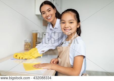 Young Asian Mother Teaching Her Daughter Housekeeping, Cleaning Kitchen Together And Smiling At Came