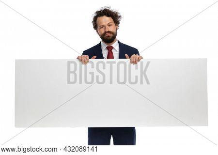 attractive businessman holding a blank billboard and feeling grumpy on white background