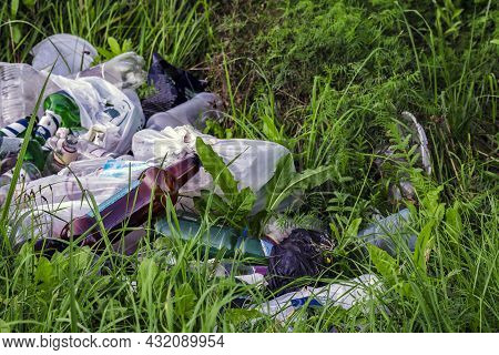 Garbage In Meadow. Rubbish, Trash Left After Picnic. People Illegally Throw Garbage Into Forest. Ill