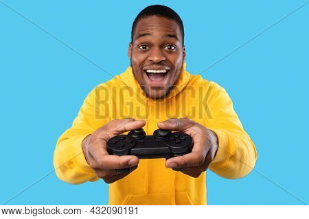 African American Guy Playing Videogame Posing With Joystick, Blue Background