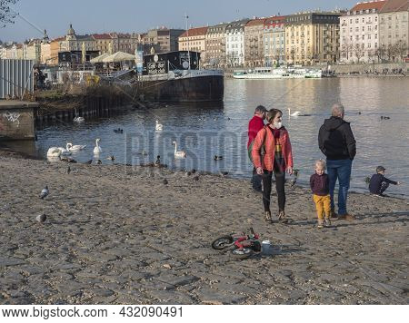 Prague, Czech Republic, March 26, 2021: People, Young Family Feed Swan, Ducks And Gulls At Embankmen