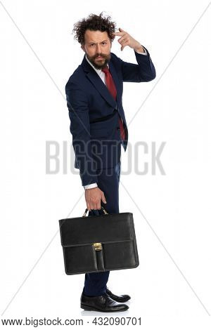side view of a handsome businessman pointing to his head and gesturing a mad sign