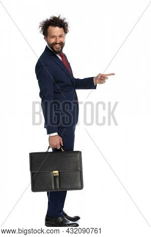 side view of a happy businessman pointing to side, smiling and holding a briefcase on white background