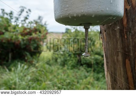 Old, Metal Washbasin Attached To A Wooden Post, In A Courtyard, In The Countryside. Rural Traditions