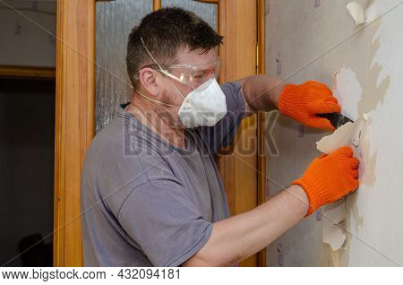 An Adult Man Removes Old Wallpaper From The Wall. The Male Is Wearing A Respirator, Safety Eyeglasse